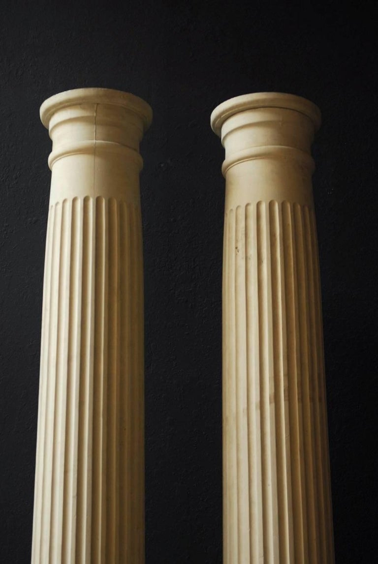 Elegant pair of fluted carved wood columns made in the Neoclassical taste. Featuring tall, fluted forms that taper from 14.5 inches to 11.5 inches wide. Mounted on square bases that accentuate the round pillars. Vintage lacquer finish shows signs of