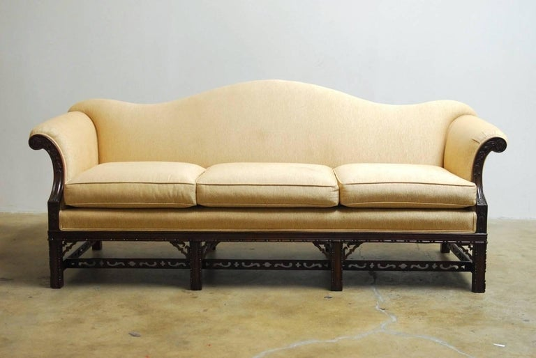 Handsome Chinese Chippendale style camel back or hump back sofa featuring a carved mahogany frame. Beautifully decorated with scrolls and quatrefoils on the cross stretchers. Supported by eight square legs with carved designs. The frame is generous
