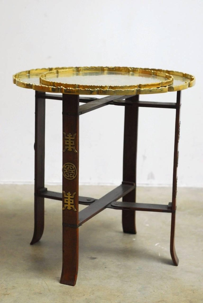 Interesting Asian folding brass tea tray table or drink table. Featuring a folding four leg base supporting two round trays. Each brass tray is incised with a decorative scene and a galleried edge with a scalloped detail. The smaller tray measures