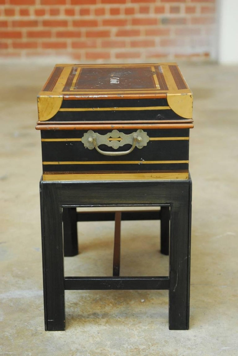 Rare British colonial officer's campaign field desk on stand. Constructed from metal and brass featuring a royal blue painted finish with gilt highlights. The top opens to a fitted interior complete with storage bins and cutglass ink wells with
