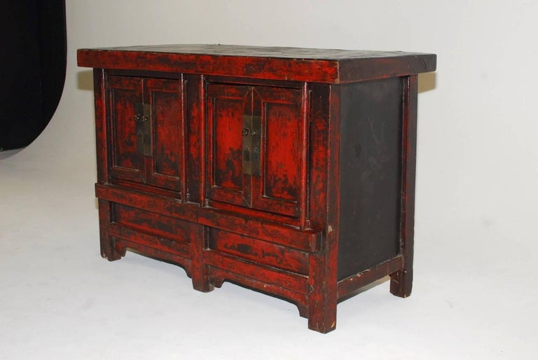 Rustic 19th century Chinese provincial coffer featuring a thick distressed red lacquer finish. The cabinet is fronted by two sets of doors opening to a two shelf interior. Produced from antique wood having wooden hinged doors. The top panel has dark