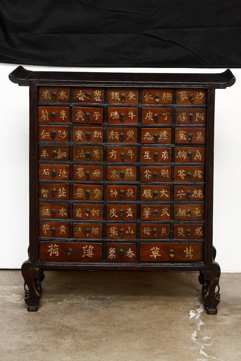Rare pair of 19th Century Chinese Qing Dynasty apothecary cabinets or herbal medicine chests. Each matching chest has 43 drawers and features an altar style scroll top case. The cabinets are supported by curved legs with decorative faux bamboo motif