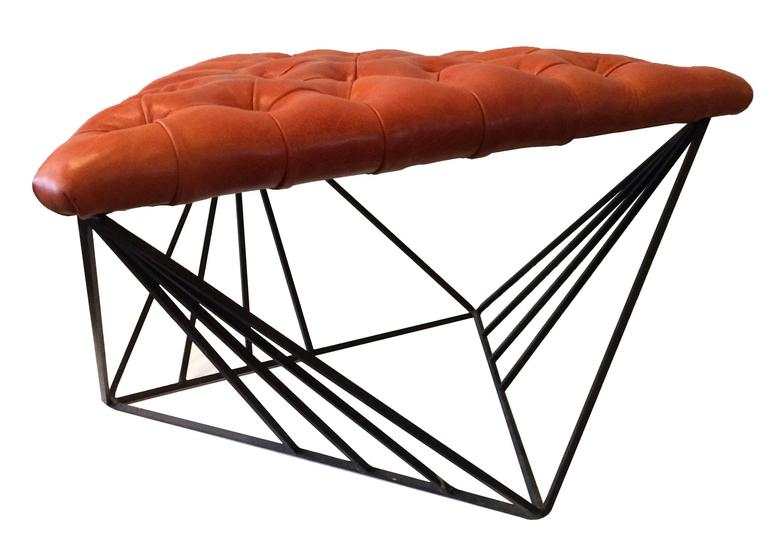 Ottoman with striking, geometric base with newly upholstered, tufted leather, triangular seat.