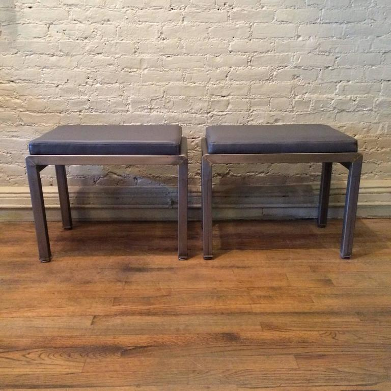 Pair of Art Deco ottomans or stools by Norman Bel Geddes for Simmons furniture company are brushed steel with newly upholstered vinyl tops.