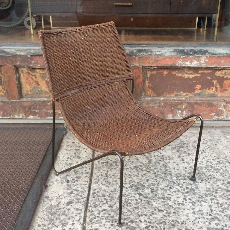 Low Slung, Lounge, Slipper Chair Is Wrought Iron And Woven Rattan.