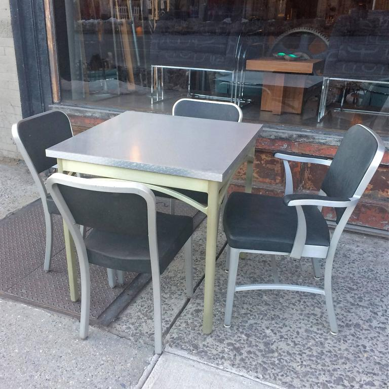 Mid-Century, brushed aluminium, dining or kitchen set by GoodForm, The General Fireproofing Co. features a square table with newly laminated top and four chairs upholstered in black textured vinyl. There are three side chairs and one armchair that