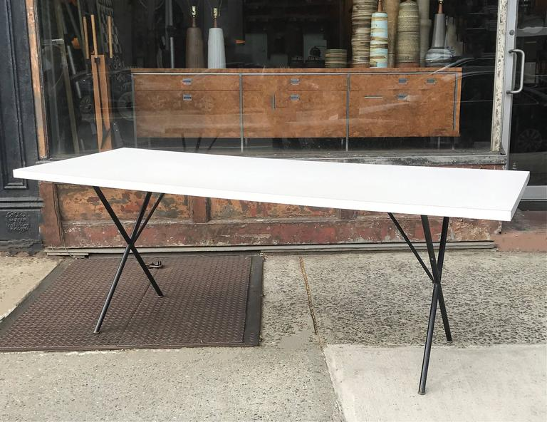 Mid-Century Modern, long, dining or work table designed by George Nelson for Herman Miller features a white laminate top with painted black iron