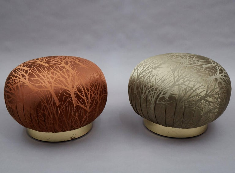 Pair of round, souffle pouf ottomans in the manner of Karl Springer feature newly upholstered seats in contrasting rust and moss, branch motif jacquard that swivel on brass bases.