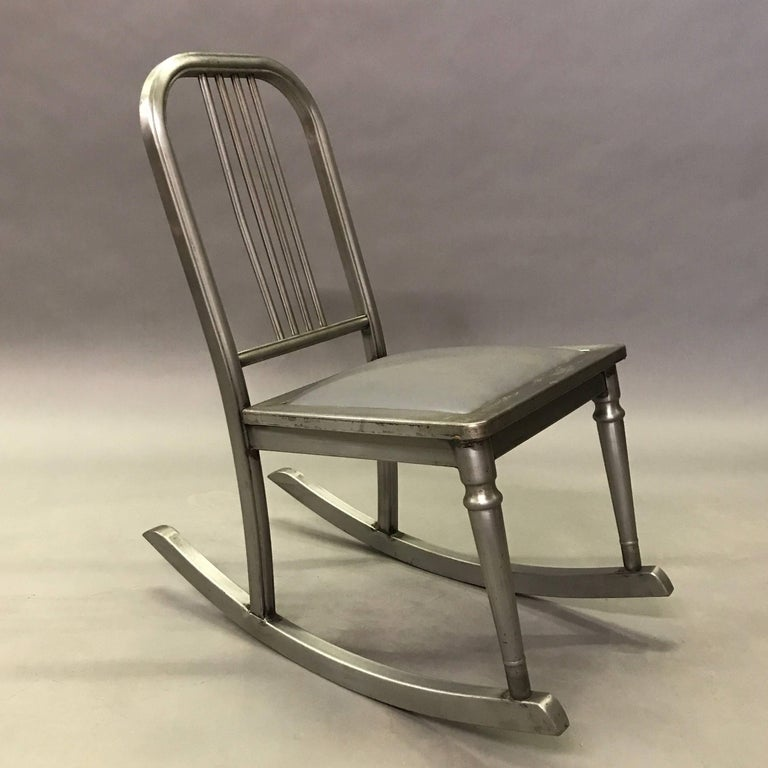 Petite, Industrial, brushed steel rocking chair with upholstered gunmetal vinyl seat is from the Sheraton Series by Simmons Company Furniture, circa 1920s.
