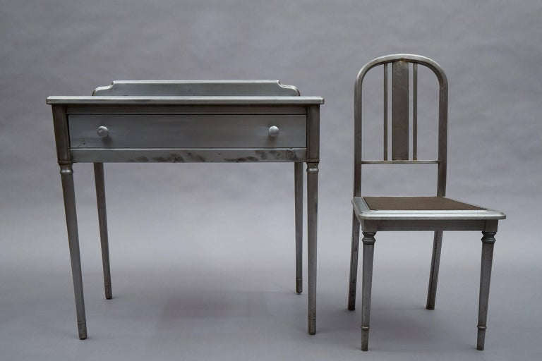 1930s, industrial, pressed, brushed steel vanity or writing desk by Simmons Company Furniture, Sheraton Series, includes beautifully detailed, rare, matching side chair with steel mesh seat.  Desk measures: 32in. W X 19in. D X 32in. HT, clearance to
