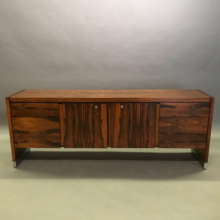 Handsome, 1970s, rosewood veneer, office credenza with chrome details features four drawers and center shelving storage in the center. The back is finished so the credenza can float in a room.