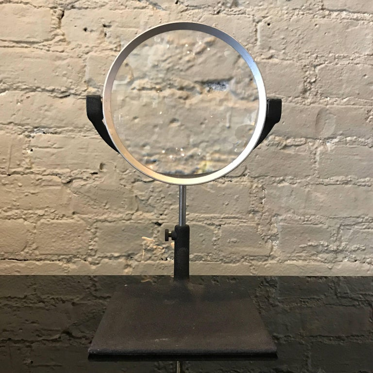 Industrial, 1940s, tabletop magnifying glass by B.M. Levoy Inc., New York City features a square, shrink paint, iron base that the round, aluminum frame magnifying glass rests in. The glass swivels and rotates 360 degrees and is height adjustable