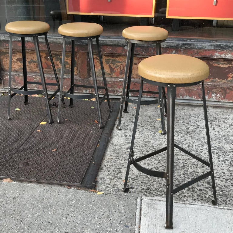 Set of four, 1940s, Industrial, barstools are newly upholstered in a faux-ostrich vinyl on stripped, angle iron bases. Seats are 14in. diameter.