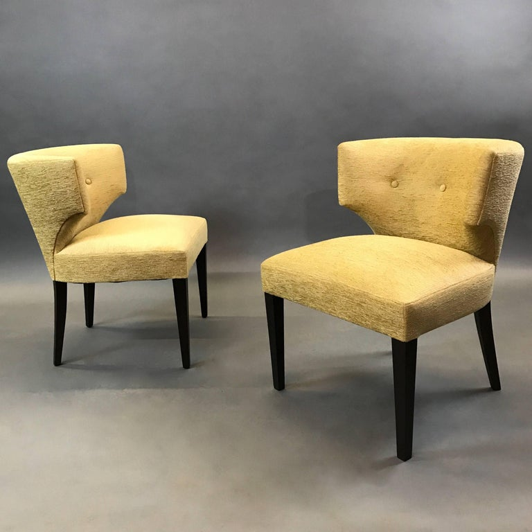 Pair of midcentury, Hollywood Regency, slipper chairs in a Grecian Klismos motif are newly upholstered in buttery chenille with contrasting, black lacquered legs.