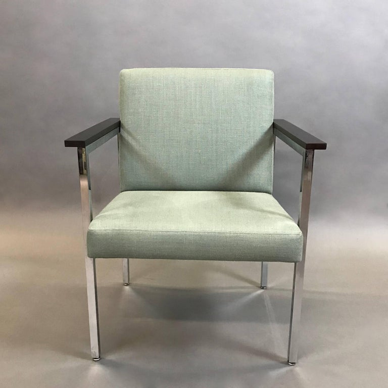 Mid-Century Modern, 1970s, chrome framed armchair features ebonized maple armrests and newly upholstered seat and back in a moss green, cotton linen blend.