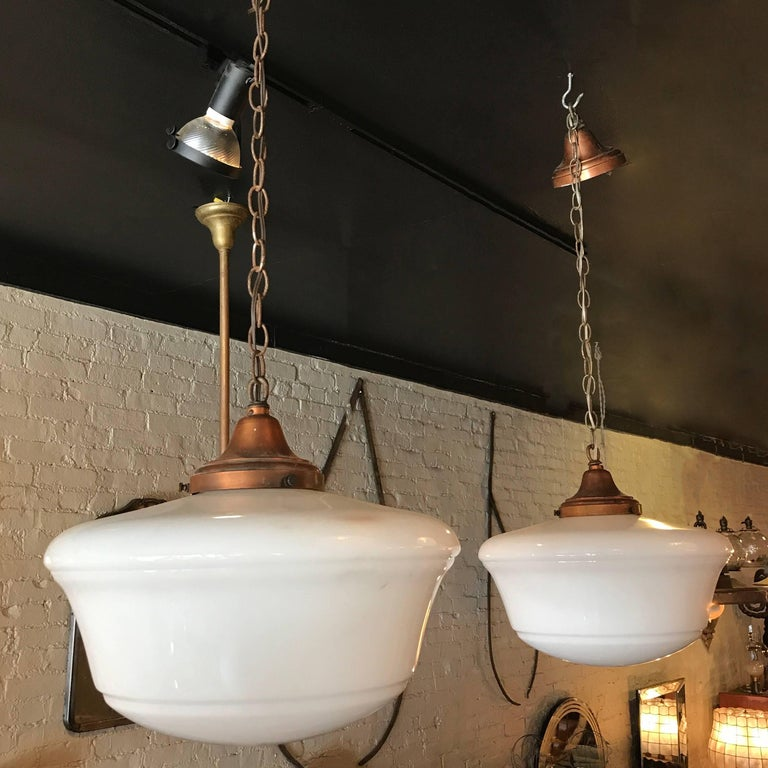 Pair of Art Deco, library pendant lights feature milk glass shades with copper fitters, 36