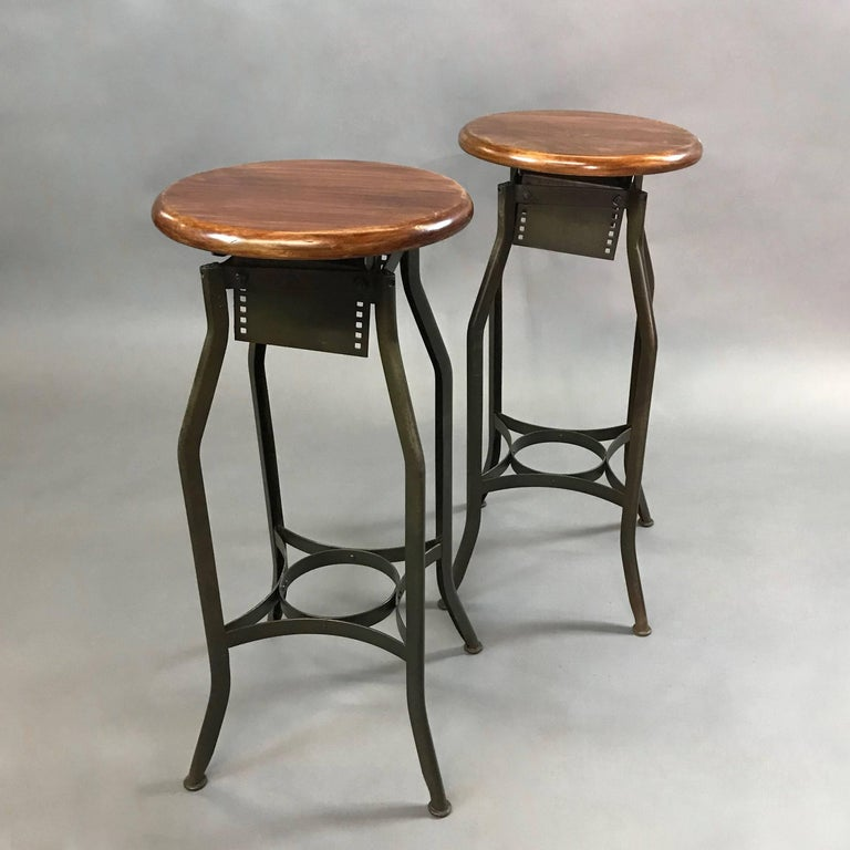 Pair of Industrial shop stool by Toledo Metal Furniture Co. feature stained pine seats and painted steel frames. The seat diameter is 14 inches and the foot print is 20 inches. The stools are height adjustable from 30 - 34 inches by unscrewing the
