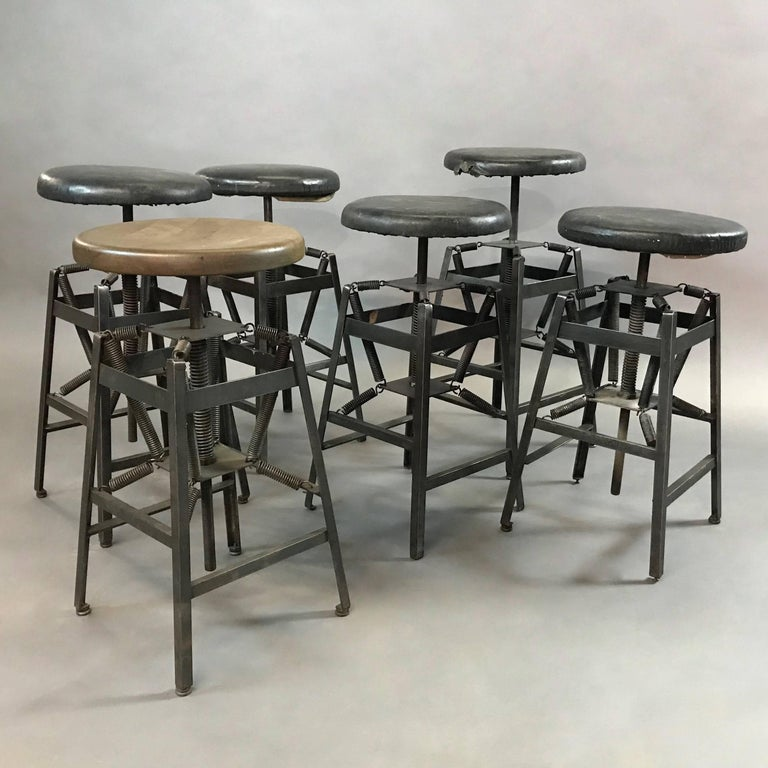 Industrial drafting stool designed by Charles E. Miller for American Cabinet Co. features an adjustable height, steel, spring suspension base with original black vinyl seats. The seats can be re-upholstered or changed to wood. Seat diameter and foot