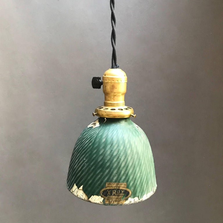 Industrial, factory pendant light features an X-Ray mercury glass dome shade with painted green exterior and brass switch fitter. The pendant is newly wired with 36 inches of black braided cloth cord to accept up to a 150 watt bulb.