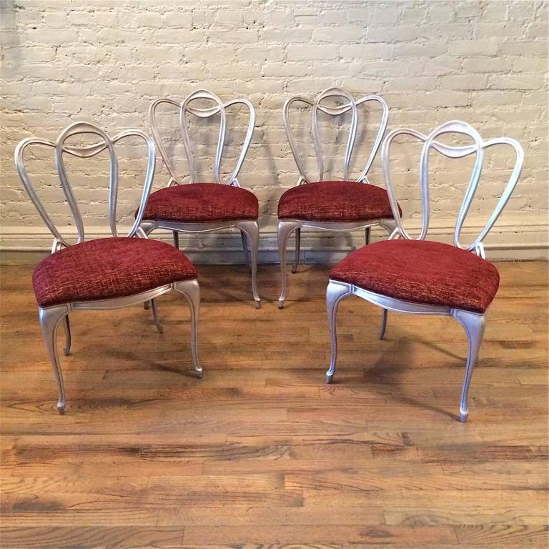 Set of four, Hollywood Regency, Art Nouveau, chairs with organic, vine motif, cast aluminum frames are newly upholstered in a rich, contrasting, burgundy, gold velvet. The Vitrolite table shown is listed separately.