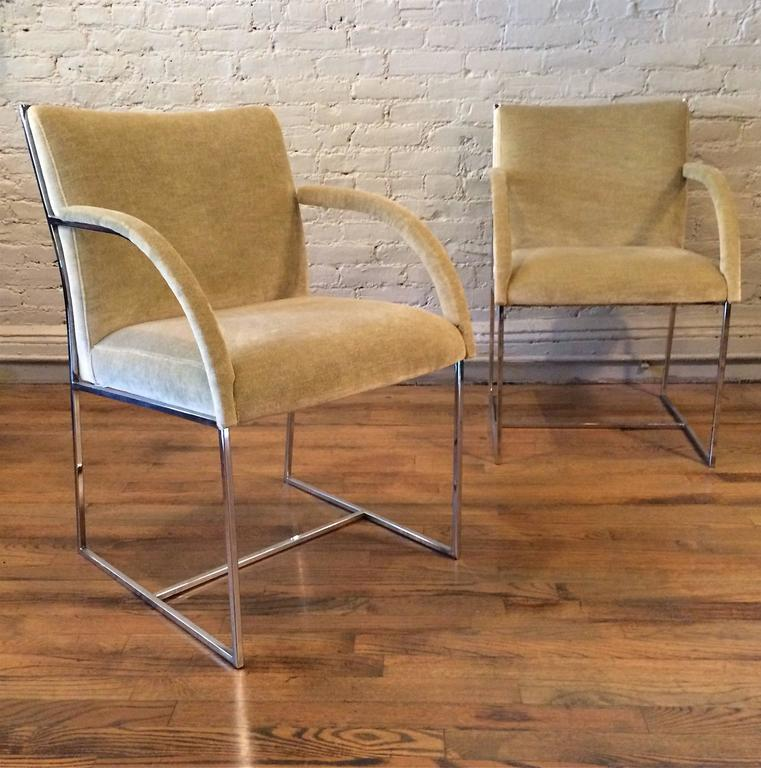 Pair of Mid-Century Modern armchairs in the style of Milo Baughman feature chrome frames newly upholstered in light pistachio green velvet.
