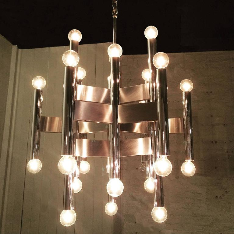 Italian modernist chrome chandelier attributed to Gaetano Sciolari has alternating tubular stems connected by flat panels.  The fixture is 18.5in diameter x 25.5in height, overall height with chain is 32in.