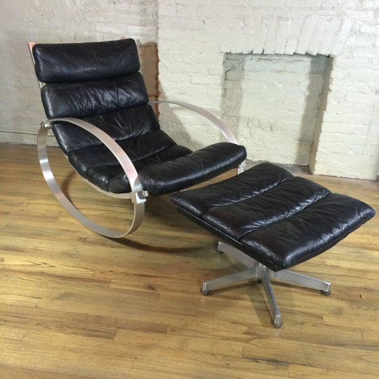 Modernist rocking lounge chair with matching ottoman designed by Hans Kaufeld, Germany features it's original black leather rolled upholstery with brushed steel frame.