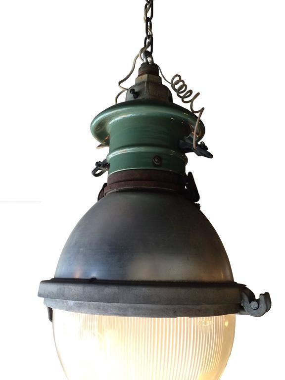 Impressive and rare, Industrial, street light pendant with cast iron and green porcelain fitter, spun aluminum dome casing and Holophane glass shade. Glass shade has Holophane logo in raised lettering with