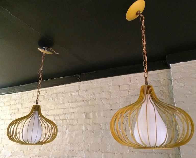 Pair of Mid-Century pendant lights are painted yellow, onion shaped, metal frames with floating frosted glass shades and matching canopies.  Measurements: pendants are 12 inch diameter and 12 inch height, height to canopies is 20 inches