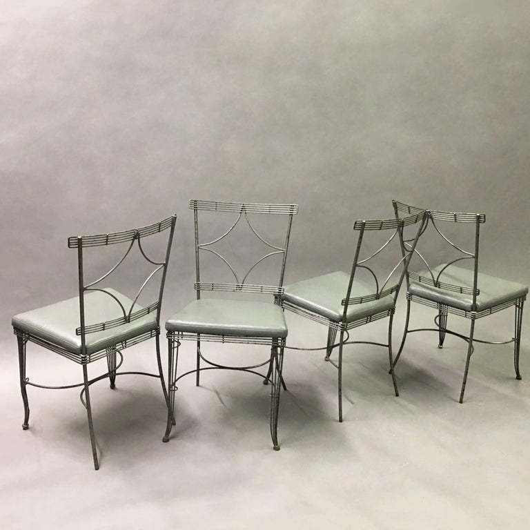 Wonderful set of four, midcentury, Hollywood Regency dining chairs feature brushed steel wire frames with diamond backs and newly upholstered seats in gray vinyl. This set is perfect for a sunroom but not recommended for outdoor use.