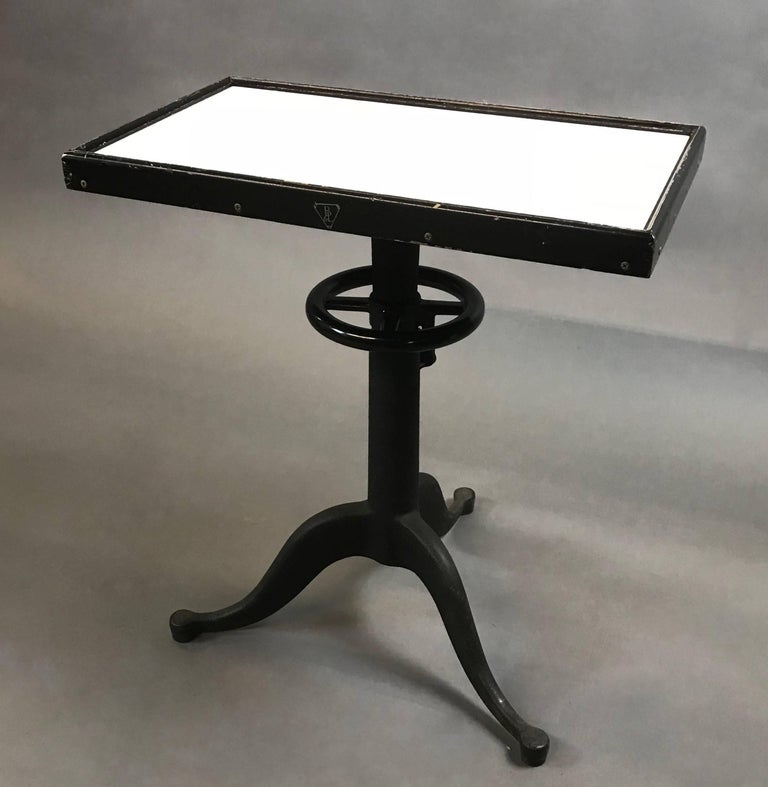 Industrial, optometry examination, table by Bausch & Lomb features a milk glass top in a wood frame atop a height-adjustable, pedestal cast iron and steel base.