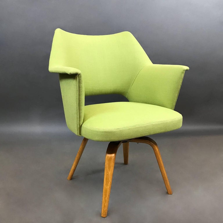 Mid-Century Modern, swivel armchair by Thonet features bright green cotton linen upholstery atop a bent maple, four leg base. Arm height is 25.5 in.