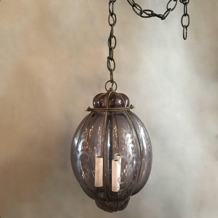 Italian, amethyst colored, Seguso, Murano glass pendant light, handblown within an iron cage features three candelabra bulbs that can accept 40 watt bulbs each on 24 in of chain.