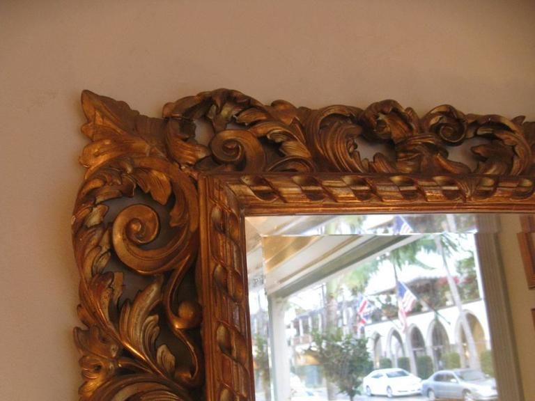 French carved giltwood mirror  Napoleon III period. Elaborated carving of scrolls and leaves. 7' wide carving around a fluted /ribbon design straight frame.