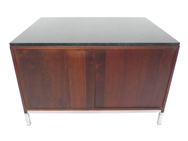 This Midcentury cabinet is in the style of Florence Knoll, whose Minimalist designs made use of simple shapes and clean lines. The cabinet consists of a black marble top, a rosewood body, a chrome base, and brass hardware. The rosewood is a rich