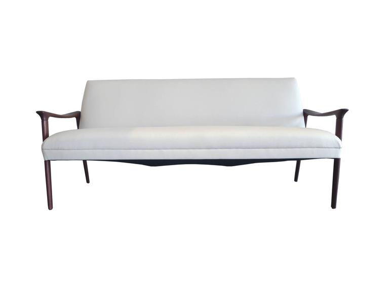 This handsome mid-20th century Danish sofa is by Ole Wanscher. It's newly refinished and reupholstered in white vinyl. The frame is a rich red-brown teak; its design is one of clean lines and soft edges. The arms are flat and elegantly slope, while