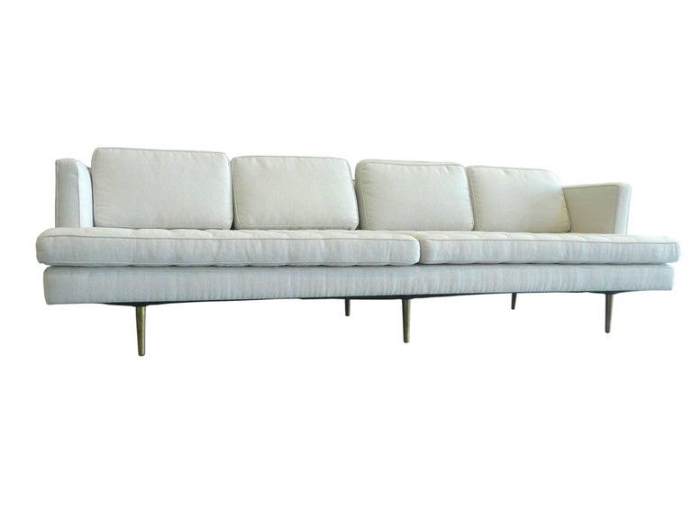 This sofa was designed by Edward Wormley for Dunbar. It is newly reupholstered in an oatmeal-white cotton bouclé. Like many of Wormley's modern designs, this sofa has clean, Stark lines punctuated by subtle decorative elements. They include the six