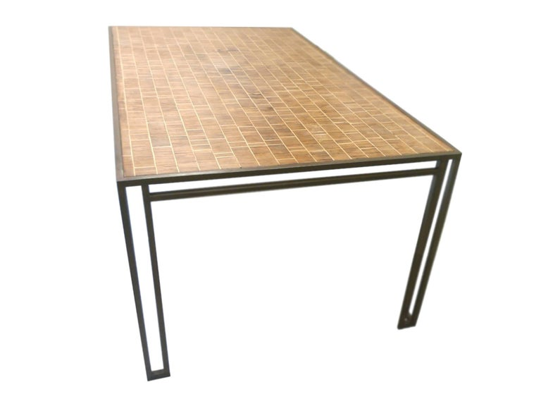 This 1970s dining table was designed by American interior decorator Billy Baldwin. It is comprised of an iron base and wood inlay top. The design is simple and elegant: the base makes use of slick Art Deco lines in its openwork structure, while the