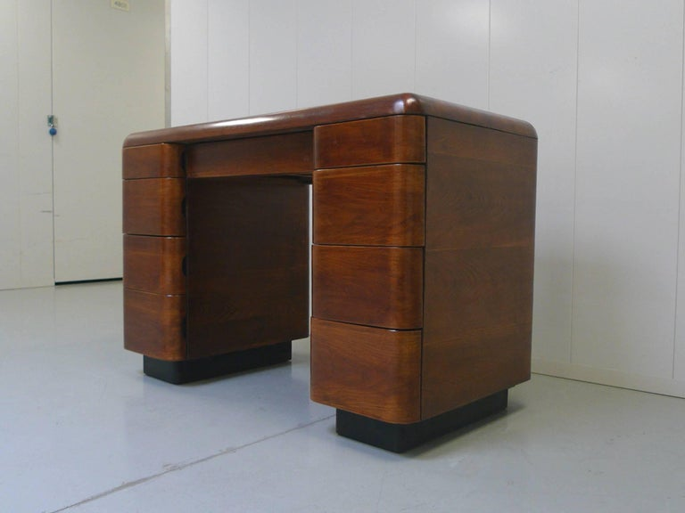 This Art Deco-style desk was designed by Paul Goldman in 1946 for Plymodern Furniture. Goldman was renowned for his use of bent plywood. The process of Plymold allowed for the beautiful curves of this Tanker-like desk to be formed. The bentwood is