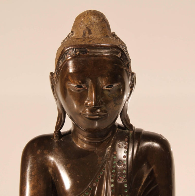 A mid-19th century Mandalay period Thai bronze Buddha inlaid with green glass and having enamel inlaid eyes. The head dress once lacquered and gilded, now with traces of lacquer. The left hand cast separately and held in place with lead. Many