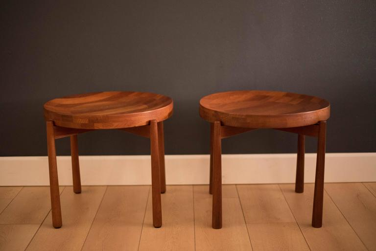 Mid-Century pair of staved side tables for Dux in solid teak. The tabletop is removable and rests on a sculpted teak base.