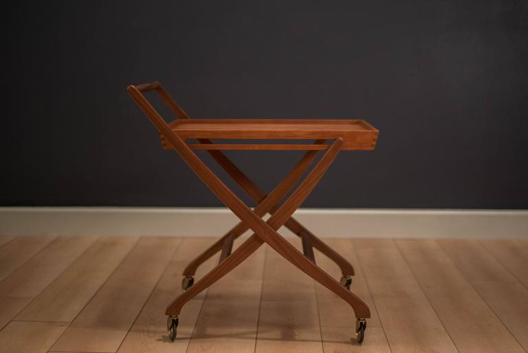 Mid-Century Danish bar cart or serving tray in solid teak. This well-crafted piece displays unique scissor legs and a dovetailed serving tray. Folds up for easy storage.