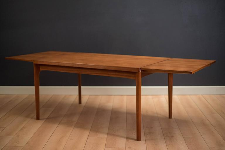 Danish modern dining table designed by Henning Kjaernulf for Vejle Stole-og Mobelfabrik in teak. This piece has two expandable leaves that tuck away neatly underneath the table when not in use. In great condition with minimal vintage