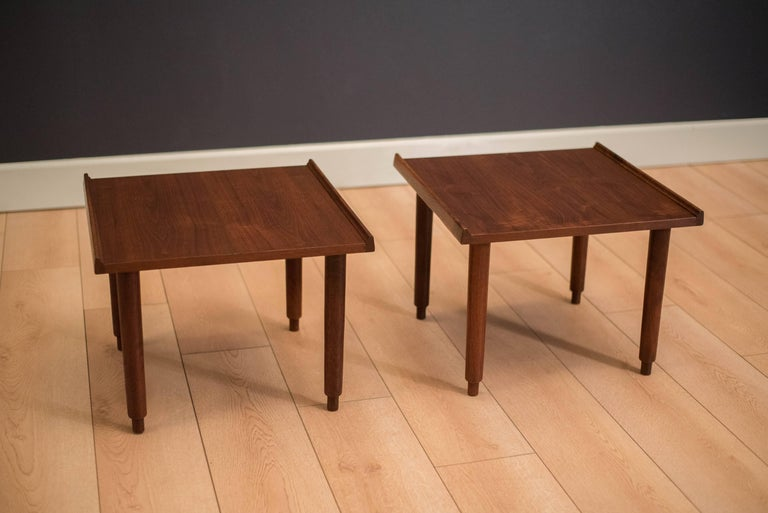 Mid-century California Modern side tables by Charles Pechanec in walnut. This pair features sculpted raised edges and unique legs. Price is for the pair.