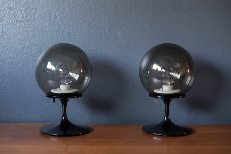 Vintage pair of stemlite lamps by Bill Curry for Design Line. This set features smoked glass globes and a tulip base with black enamel finish.
