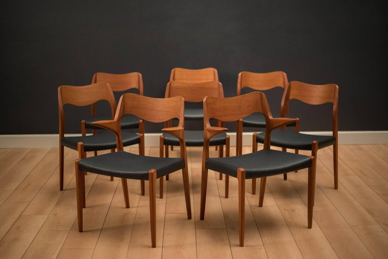 Mid century set of eight Danish dining chairs by Niels Møller for J.L. Møller Møbelfabrik in teak. This set includes six model 71 side chairs and two 55 armchairs. Seats have been professionally reupholstered in a navy blue leatherette. Price is for