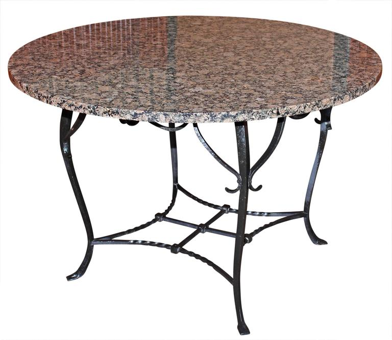 Antique wrought iron and granite  dining table. Base is handmade. Table is strong and solidly built. Made circa 1910. Table may be used indoors or outdoors.