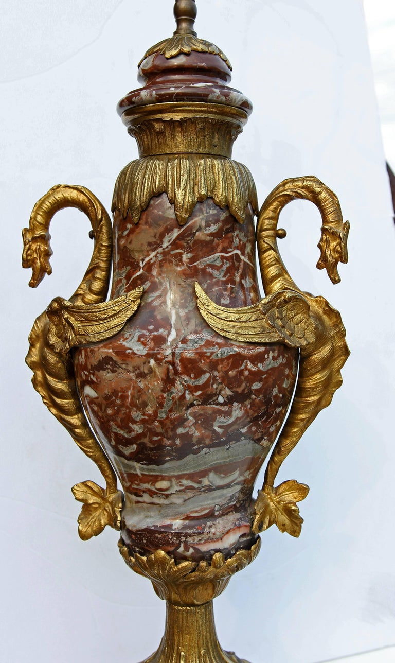 "Pair of 19th century style variegated marble lamps with brass mounts. Good quality castings. Includes good sized finials. Over all height with harp and finial is 40"". Height to top of socket is 28"". Height to top of urns is 22 1/2"" high."