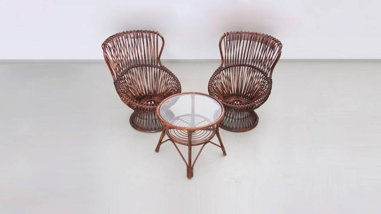Rare set of two armchairs with rattan frame by Franco Albini for Vittorio Bonacina. Small round table available with glass top. Margherita won the gold medal prize at the IX Triennale, Milano.