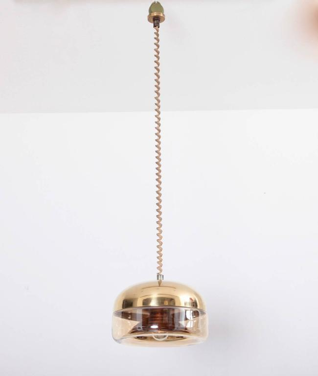 Beautiful Castiglioni style high quality brass and glass pendant with a height adjustable role system that is dated 1972. The glass has a gold plating and the top is solid brass.  Original cable and one x E27 / model a bulb. To be on the safe side,